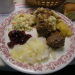 Clockwise from the top: mashed potatoes and gravy, rutabaga, meatballs, lutefisk with melted butter, cranberry sauce and coleslaw